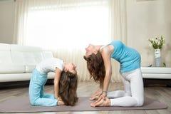 做与她的一点daughte的怀孕的少妇产前瑜伽 免版税库存照片