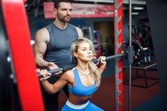 做与她的个人教练员协助的运动的女孩矮小锻炼在健身房 免版税库存图片