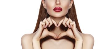 做与她的手指的浪漫少妇心脏形状 爱和情人节标志 有愉快的微笑的时尚女孩 免版税图库摄影