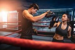做与她的教练的年轻妇女kickboxing的训练 免版税库存照片