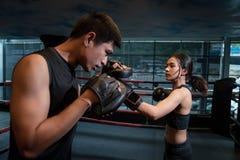 做与她的教练的年轻妇女kickboxing的训练 免版税图库摄影