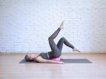 做与小桃红色健身球的美丽的yong妇女pilates锻炼,腿曲拱锻炼 室内,顶楼背景 免版税图库摄影