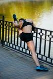 做与左腿的oung运动wooman的后面看法舒展锻炼在栏杆,在奔跑以后 免版税库存照片