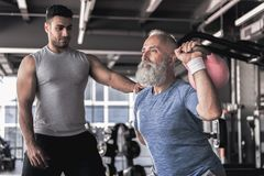 做与年轻辅导员的资深男性锻炼现代健身房的 库存照片