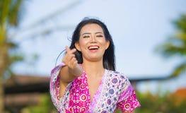 做与手指的爱标志和手的年轻愉快的美丽的亚裔中国旅游妇女摆在和嘲笑海滩热带reso 库存照片