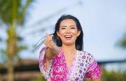 做与手指的爱标志和手的年轻愉快的美丽的亚裔中国旅游妇女摆在和嘲笑海滩热带reso 免版税库存照片
