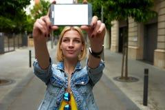 做与手机数字照相机的旅游妇女自画象在她的假期假日期间在夏天 免版税图库摄影