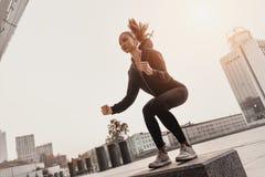 做与扔石头的步平台的年轻女人腿部锻炼 免版税图库摄影