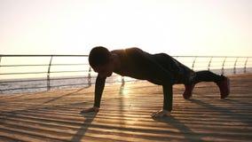 做与拍手的年轻运动员俯卧撑户外在前面的木froor海或海洋 早晨太阳 健身 股票录像