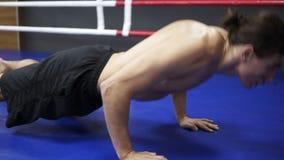 做与拍手的年轻高运动员俯卧撑户内在拳击的froor 健身和行使,拳击训练 影视素材