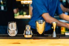 做与振动器、双重大小火簸机和水杯的酒吧调酒员鸡尾酒与冰块在鸡尾酒柜台酒吧 免版税库存图片