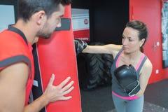 做与教练的年轻妇女kickboxing的训练 免版税库存图片