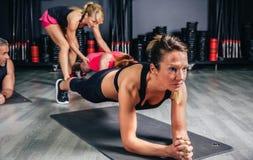 做与教练员的妇女俯卧撑在背景中 免版税库存图片