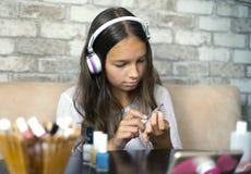 做与文件的耳机和家庭衣裳听的音乐的逗人喜爱的女孩修指甲擦亮的钉子 库存照片