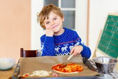 做与新鲜蔬菜的逗人喜爱的小孩男孩意大利薄饼 免版税库存照片