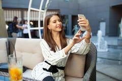 做与智能手机数码相机的年轻微笑的妇女照片,当坐在室外夏天餐馆内部,愉快的女性时 免版税库存照片