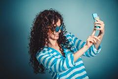 做与智能手机的妇女selfie isloated在蓝色背景 库存图片