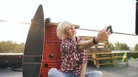 做与智能手机的愉快的白肤金发的女孩selfie照片户外在现代修造的屋顶 快乐的可爱的女性 影视素材