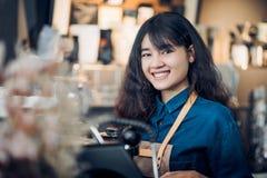 做与机器在逆酒吧和微笑的亚洲妇女barista热的咖啡在咖啡馆餐馆、食物和饮料服务的照相机 图库摄影