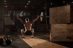 做与杠铃天花板的肌肉人蹲坐 免版税库存图片