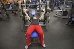 做与杠铃标尺的中年妇女卧推在健身锻炼期间 免版税库存图片