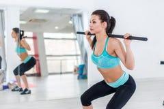做与杠铃的亭亭玉立的深色的妇女蹲坐在健身大厅里 免版税库存照片