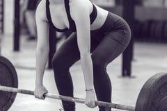 做与杠铃的体育女孩锻炼 免版税库存图片