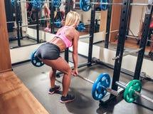 做与杠铃的健身房的少妇蹲坐 免版税库存图片