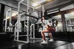 做与杠铃的健身房的年轻性感的深色的女孩蹲坐 免版税库存图片