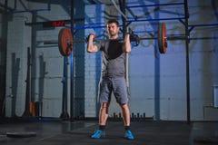 做与杠铃的大力士一锻炼在一个灰色混凝土墙的背景的健身房 免版税库存照片