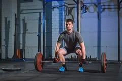 做与杠铃的大力士一锻炼在一个灰色混凝土墙的背景的健身房 免版税图库摄影