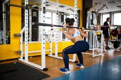 做与杠铃的女孩蹲坐在健身房 一种健康生活方式的概念 库存图片