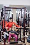 做与杠铃的少女蹲坐在健身房在教练员的监督下 库存图片