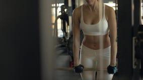 做与杠铃的斜面和看在镜子的性感的妇女在健身房俱乐部 股票视频