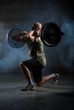 做与杠铃的秃头运动员锻炼 库存照片