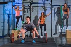 做与杠铃的肌肉人蹲坐在健身房,美丽的女孩在背景中 免版税库存照片