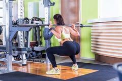 做与杠铃的适合的妇女蹲坐在健身房 免版税库存照片