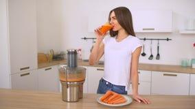 做与榨汁器的妇女红萝卜汁 新鲜做汁液由红萝卜 准备从红萝卜的女孩新鲜的汁液 影视素材