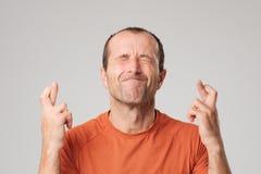 做与横穿手指的成熟西班牙人一个愿望标志被隔绝在背景 库存图片