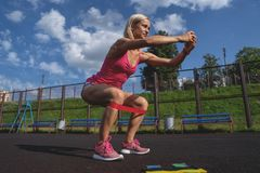 做与橡皮筋儿的年轻运动的妇女锻炼室外 库存照片