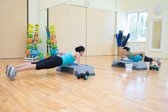 做与步进的美丽的亭亭玉立的妇女俯卧撑在健身房 免版税库存图片