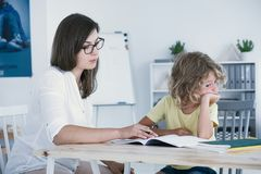 做与母亲的顽皮男童家庭作业在类以后 图库摄影