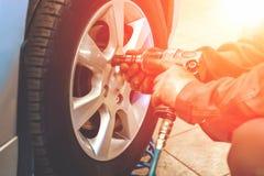 做与气动力学的板钳的汽车修理师工作者轮胎或轮子替换在修理服务站车库,阳光作用 图库摄影