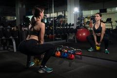 做与水壶响铃的可爱的白肤金发的女孩锻炼 举重、十字架适合的和力量举的锻炼 体育,健身conce 库存图片