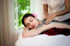 做与治疗泥的男按摩师按摩温泉在泰国温泉生活方式的亚裔妇女身体,因此放松和豪华 免版税库存照片