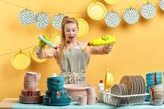 做与洗碗盘行为液体的创造性的可爱的主妇实验 免版税库存图片