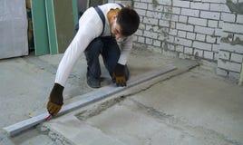做与测量的标准的建筑工人标注在工地工作 免版税库存图片