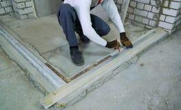 做与测量的标准的建筑工人标注在工地工作 免版税库存照片