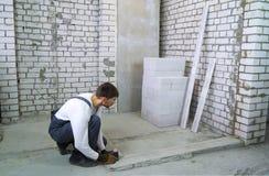做与激光水平的建筑工人措施在工地工作 库存照片