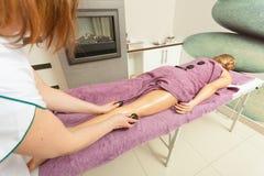 做与热的石头的女按摩师腿按摩 免版税图库摄影